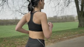 Young sport girl is running with headphones in park in summer, healthy lifestyle, sport conception, camera round move