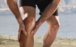 Young sport man with athletic legs holding knee in pain suffering muscle injury running. Young sport man with strong athletic legs holding knee with his hands in stock photos