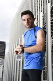 Young sport man checking time on chrono timer runners watch holding water bottle after training session Stock Photo