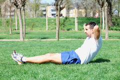 Young sport man, fitness guy making push ups exercise. Stock Photos
