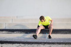 Young sport man in fluorescent bright t-shirt warming up before begin his run in early morning Stock Photo