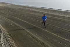 Young sport man running alone on desert beach along the sea shore training workout Stock Photography