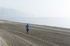 Young sport man running alone on desert beach along the sea shore training workout Stock Photos