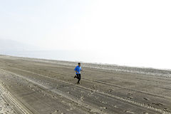 Young sport man running alone on desert beach along the sea shore training workout Royalty Free Stock Photography