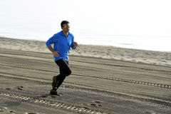 Young sport man running alone on desert beach along the sea shore training workout Royalty Free Stock Photos