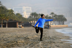 Young sport man stretching workout before running on the beach in front of  the sea early morning Stock Image