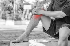 Young sport man with strong athletic legs holding knee. With his hands in pain after suffering ligament injury during a running workout training isolated on Stock Image