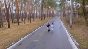 Young people running in the forest. Young sport people makes morning exercises outdoors. Pretty woman and handsome man wearing sportswear runs in the forest stock footage