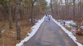 Young man and woman runs in winter forest in the morning. Young sport people makes morning exercises outdoors. Pretty woman and handsome man wearing sportswear stock video footage