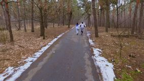 Two young people runs in the forest. Young sport people makes morning exercises outdoors. Pretty woman and handsome man wearing sportswear runs in the forest stock footage