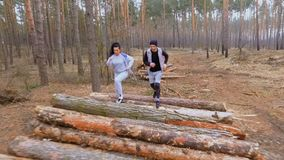 Man and woman runs along logs in the forest. Young sport people makes morning exercises outdoors. Pretty woman and handsome man wearing sportswear training in stock video