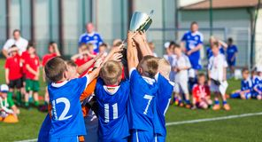 Young Sport Team with Trophy. Boys Celebrating Sports Achievement. Young Soccer Players Holding Trophy. Boys Celebrating Soccer Football Championship. Winning stock image