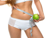 Young sport woman body measuring waist with tape measure Royalty Free Stock Image