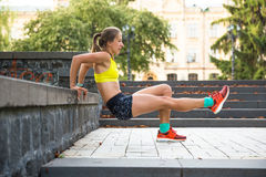 Young sport woman doing exercises during training outside in city park. Fitness model running outdoor Stock Photography