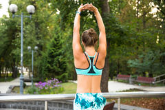 Young sport woman doing exercises during training outside in city park. Fitness model running outdoor Stock Photos