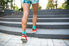 Young sport woman doing exercises during training outside in city park. Fitness model running outdoor Stock Images