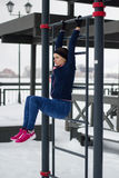 Young sport woman doing press exercises on work out fitness at snow winter park Stock Photography