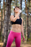 Young Sport Woman Drinking Water During Running in Beautiful Wild Pine Forest. Active Lifestyle Concept. Stock Photography