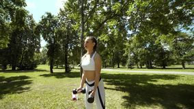 Young sport woman exercising with heavy steel dumbbell outside on nature in the park. Fitness exercise for girls stock footage