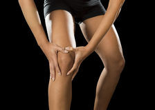 Young sport woman holding injured knee suffering pain in ligaments injury or pulled muscle stock image