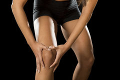 Young sport woman holding injured knee suffering pain in ligaments injury or pulled muscle royalty free stock photos