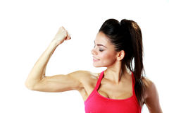 Young sport woman looking at her biceps Stock Images