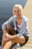 Young sport woman relax on pier water Stock Photos