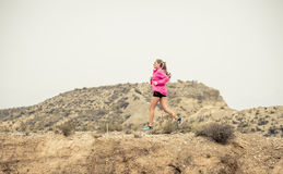 Young sport woman running off road trail dirty road with dry desert landscape background training hard Stock Images