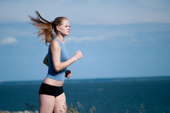 Young sport woman running on sunny day Royalty Free Stock Images