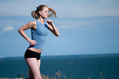 Young sport woman running on sunny day Stock Photography