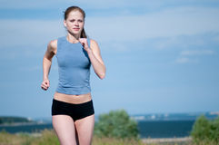 Young sport woman running on sunny day Royalty Free Stock Photography