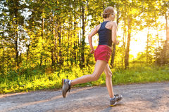 Young sport woman runs on the road Royalty Free Stock Photos