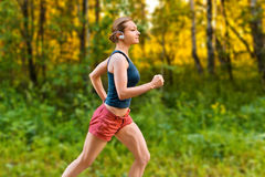 Young sport woman runs on the road Stock Images