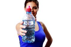 Young sport woman showing bottle with water. Focus on bottle. Stock Photos
