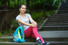 Young sport woman after a workout sitting on the stairs in the Park. Royalty Free Stock Images