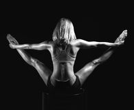 Young sport yoga woman back view posing while doing gymnastic sp Royalty Free Stock Images