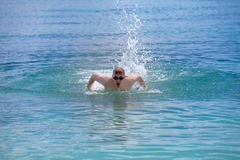 Young sporting man swims in the sea butterfly stroke style in a sunny day Stock Image
