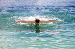 Young sporting man swims in the sea dolphin style. Portrait in a sunny day Stock Images