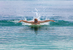 Young sporting man swims in the sea dolphin style.Portrait in a sunny day Stock Photography