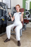 The young sporting woman in fitness center trains.Portrait in a sunny day Stock Photo