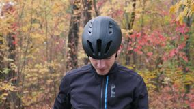 Young sportive attractive caucasian guy in black active sportswear puts on black cycling helmet and sports glasses in fall park. M. Ale cyclist puts on cycling stock video footage