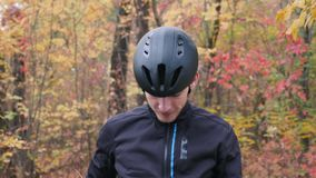 Young sportive attractive caucasian guy in black active sportswear puts on black cycling helmet and sports glasses in fall park. M. Ale cyclist puts on cycling stock footage