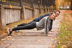Sportive guy and the girl are standing in a static lath on outstretched arms. Outdoors in the autumn park. Stock Photography