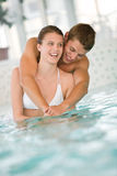 Young sportive couple have fun in swimming pool Stock Photos