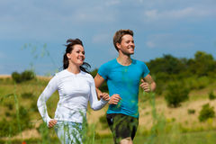 Young sportive couple is jogging outside. Young fitness couple doing sports outdoors; jogging on a green meadow in summer under a blue sky stock images