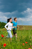 Young sportive couple is jogging outside. Young fitness couple doing sports outdoors; jogging on a green meadow in summer under a blue sky stock photography