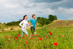 Young sportive couple is jogging outside. Young fitness couple doing sports outdoors; jogging on a green meadow in summer under a blue sky royalty free stock images