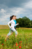Young sportive couple is jogging outside. Young fitness couple doing sports outdoors; jogging on a green meadow in summer under a blue sky royalty free stock photo