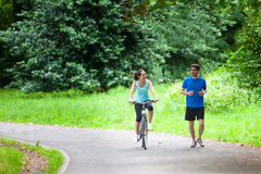 Young sportive couple jogging at the park. View of a Young sportive couple jogging at the park Royalty Free Stock Images