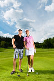 Young sportive couple playing golf on a course. Young sportive couple playing golf on a golf course, they certainly do exercise or have training Royalty Free Stock Image